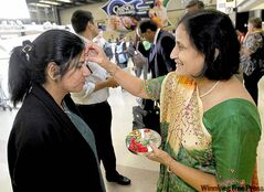 Hina Shah, right, greets trade adviser Ruchi Agarwal of Gujarat with a traditional Indian welcome.