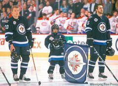 Ashton takes his spot during the national anthem beside Jets  Antti Miettinen and Tanner Glass.