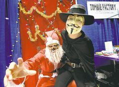Amy Loewen, dressed as V from the movie Vendetta, has her picture taken with Zombie Santa, a.k.a. Travis Cool.