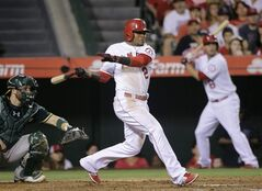 Los Angeles Angels' Erick Aybar hits an RBI-single during the fourth inning of a baseball game against the Oakland Athletics, Saturday, Aug. 30, 2014, in Anaheim, Calif. (AP Photo/Jae C. Hong)