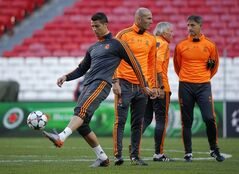 Real's Cristiano Ronaldo, foreground controls the ball as former player Zinedine Zidane looks on, during a training session ahead of Saturday's Champions League final soccer match between Real Madrid and Atletico Madrid, in Luz stadium in Lisbon, Portugal, Friday, May 23, 2014. (AP Photo/Andres Kudacki)