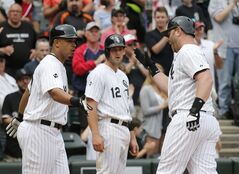 Chicago White Sox's Jose Abreu, left, and Conor Gillaspie (12) greet Adam Dunn at home after the trio scored on Dunn's home run off San Francisco Giants starting pitcher Tim Hudson, during the fifth inning of an interleague baseball game Wednesday, June 18, 2014, in Chicago. (AP Photo/Charles Rex Arbogast)