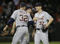 Detroit Tigers starter Max Scherzer, right, celebrates with catcher Bryan Holaday and Don Kelly (50) after the Tigers defeated the Chicago White Sox 4-0 in a baseball game in Chicago on Thursday, June 12, 2014. (AP Photo/Nam Y. Huh)
