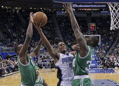 Orlando Magic's Arron Afflalo (4) gets off a shot between Boston Celtics' Jeff Green, left, and Brandon Bass, right, during the first half of an NBA basketball game in Orlando, Fla., Sunday, Jan. 19, 2014.(AP Photo/John Raoux)