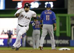 Miami Marlins' Rafael Furcal, left, rounds second base after hitting a triple against the New York Mets in the first inning of a baseball game in Miami, Friday, June 20, 2014. (AP Photo/Alan Diaz)