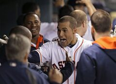 Houston Astros' George Springer, center, celebrates in the dugout after hitting a two-run homer against the Texas Rangers in the seventh inning of a baseball game Wednesday, May 14, 2014, in Houston. (AP Photo)