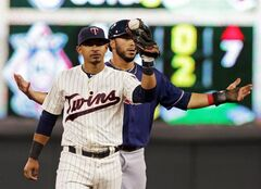 Minnesota Twins shortstop Eduardo Escobar, left, holds up the ball while Cleveland Indians' Mike Aviles questions an out call on a steal attempt in the fourth inning of a baseball game, Wednesday, Aug. 20, 2014, in Minneapolis. After the play was reviewed, Aviles was ruled safe. (AP Photo/Jim Mone)