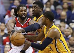 Washington Wizards forward Nene, left, passes around Indiana Pacers center Roy Hibbert (55) and forward Paul George (24) during the second half in Game 6 of an Eastern Conference semifinal NBA basketball playoff series in Washington, Thursday, May 15, 2014. (AP Photo/Alex Brandon)