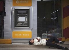 In this Feb. 24, 2009 photo, a man sleeps next to an Evergrowing Bank ATM machine in Chengdu. THE CANADIAN PRESS/AP, files