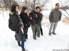 JOE.BRYKSA@FREEPRESS.MB.CA  Dad Daniel Thorassie, centre, breaks down Sunday afternoon on the bank of the Red River where his six-year-old son Nathaniel disappeared the day before.