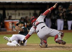 Oakland Athletics' Alberto Callaspo, left, scores past Los Angeles Angels catcher Hank Conger on a triple by Sam Fuld during the sixth inning of a baseball game Friday, Aug. 22, 2014, in Oakland, Calif. (AP Photo/Marcio Jose Sanchez)