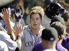 Colorado Rockies' Corey Dickerson is congratulated in the dugout after a solo home run off Cleveland Indians relief pitcher Scott Atchison in the seventh inning of a baseball game Saturday, May 31, 2014, in Cleveland. (AP Photo/Mark Duncan)
