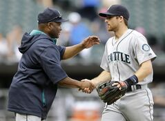 Seattle Mariners manager Lloyd McClendon, left, celebrates with shortstop Brad Miller after the Mariners defeated the Chicago White Sox 3-2 in a baseball game in Chicago on Saturday, July 5, 2014. (AP Photo/Nam Y. Huh)