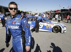Carl Edwards walks as his crew pushes his car back to the garage after his qualifying run for the Daytona 500 NASCAR Sprint Cup Series auto race at Daytona International Speedway in Daytona Beach, Fla., Sunday, Feb. 16, 2014. (AP Photo/John Raoux)