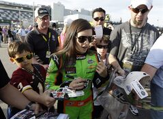 Danica Patrick signs autographs for fans after her qualifying run for Saturdays NASCAR Nationwide Series auto race, Friday, Feb. 22, 2013, at Daytona International Speedway in Daytona Beach, Fla. (AP Photo/Chris O'Meara)