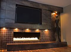 Porcelain tiles of differing sizes, supplied by Ames of Winnipeg, cover the wall that surrounds the inset fireplace and add a modern flair. The old brick fireplace before the renovation, below, was dated.