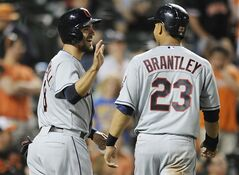 Cleveland Indians' Lonnie Chisenhall, left, and Michael Brantley celebrate after scoring on a double by Carlos Santana to take the lead against the Baltimore Orioles in the 13th inning of a baseball game, Thursday, May 22, 2014, in Baltimore. The Indians won 8-7 in 13 innings.(AP Photo/Gail Burton)