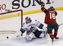 Minnesota Wild left wing Jason Zucker (16) scores against Vancouver Canucks goalie Cory Schneider (35) during the first period of an NHL hockey game Sunday March 10, 2013 in St. Paul, Minn. (AP Photo/Genevieve Ross)