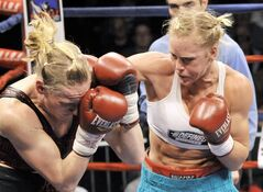 FILE-In this Dec. 2, 2011 file photo, Anne Sophie Mathis of Dombasle-sur-Meurthe, France, left, gets hit by Holly Holm, during the IBA and WBAN Welterweight title fight in Laguna, N.M. The world's former No. 1-rated female boxer has signed with the Ultimate Fighting Championship. UFC President Dana White tweeted last week that Albuquerque fighter Holm has agreed to terms with the world's largest mixed martial arts promotion. (AP Photo/The Albuquerque Journal, Greg Sorber,File)