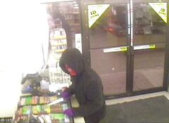 Picture from video surveillance shows robber holding knife.