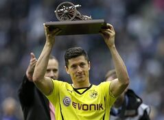 Dortmund's Robert Lewandowski of Poland lifts the goal-getter trophy after the German Bundesliga soccer match between Hertha BSC Berlin and Borussia Dortmund in in Berlin, Germany, Saturday, May 10, 2014. (AP Photo/Michael Sohn)