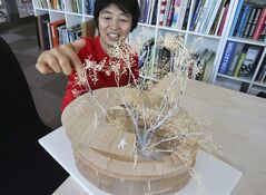 In this July 15, 2014 photo, architect Yui Tezuka speaks with a model of a building she designed during an interview at her office in Tokyo. Yui and her husband Takaharu Tezuka designed Fuji Kindergarten in Tachikawa, outside Tokyo, which like other designs by rising architects also illustrates the idea of fusing the outside with the inside. The walls of the doughnut-shaped building are of glass, and they open as sliding doors, making the courtyard an integral part of the child's every day. The spherical roof is a playground, for the children to run around and around. The couple often uses the roof for living space, and they swear sitting side by side on a sloped surface, like a riverbank, as opposed to facing each other across a table, is good for human relations.(AP Photo/Koji Sasahara)