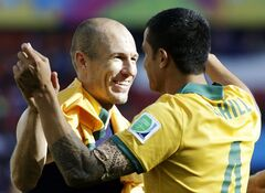 Netherlands' Arjen Robben, left, hugs Australia's Tim Cahill following the team's 3-2 loss to the Netherlands during the group B World Cup soccer match between Australia and the Netherlands at the Estadio Beira-Rio in Porto Alegre, Brazil, Wednesday, June 18, 2014. (AP Photo/Fernando Vergara)