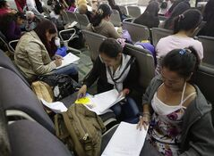 Overseas Filipino Workers (OFW), fill out documents upon arrival Saturday, March 9, 2013 in Manila, Philippines, from civil war-torn Syria. On Wednesday, a convoy of 21 peacekeepers were seized near the Syrian village of Jamlah, just a mile from the Israeli-controlled Golan Heights in an area where the U.N. force had patrolled a cease-fire line between Israel and Syria without incident for nearly four decades, with UN and Philippine Foreign Affairs officials are negotiating for their safe release. The Syrian rebels want the Red Cross to escort them out of the area because of fighting with Syrian government forces, the Philippine military said. (AP Photo/Bullit Marquez)