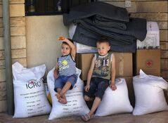 Iraqi children sit atop bags of rice donated by the International Committee for the Red Cross, in Alqosh, Sunday, June 15, 2014. THE CANADIAN PRESS/AP