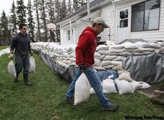 Ted  Bray, right, and his son John do last-minute  sandbagging at  their home near Oakville. Their home is next to the Elm River.