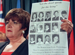 Priscilla de Villiers holds up a photo of the 14 women killed by gun violence at the Ecole Polytechnique in Montreal, during a news conference in Ottawa in 1998.