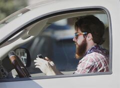 An man works his phone as he drives through traffic in Dallas, Tuesday, Feb. 26, 2013. A study shows the most dangerous manoeuvre a driver can ever perform is make a left turn while chatting on a cellphone. THE CANADIAN PRESS/AP/LM Otero