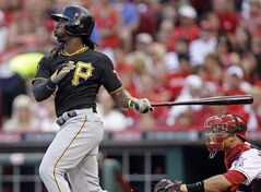 Pittsburgh Pirates' Andrew McCutchen hits a solo home run off Cincinnati Reds starting pitcher Mat Latos in the fourth inning of a baseball game, Friday, July 11, 2014, in Cincinnati. Devin Mesoraco catches at right. (AP Photo/Al Behrman)