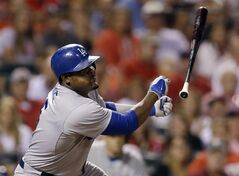 Los Angeles Dodgers' Juan Uribe loses his bat as he pops out in foul territory to St. Louis Cardinals catcher Tony Cruz to end the top of the eighth inning of a baseball game Friday, July 18, 2014, in St. Louis. (AP Photo/Jeff Roberson)