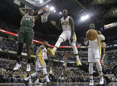 Milwaukee Bucks' Khris Middleton (22), Indiana Pacers' Lance Stephenson (1) and Indiana Pacers' Roy Hibbert watch as a ball goes out-of-bounds during the first half of an NBA basketball game on Thursday, Feb. 27, 2014, in Indianapolis. (AP Photo/Darron Cummings)