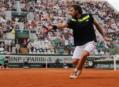 Latvia's Ernests Gulbis returns the ball to Tomas Berdych of the Czech Republic during their quarterfinal match of the French Open tennis tournament at the Roland Garros stadium, in Paris, France, Tuesday, June 3, 2014. Gulbis won 6-3, 6-2, 6-4. (AP Photo/David Vincent)