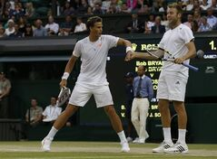 Vasek Pospisil of Canada, left, and Jack Sock of the U.S celebrate a point during the men's doubles final against Bob Bryan and Mike Bryan of the U.S at the All England Lawn Tennis Championships in Wimbledon, London, Saturday, July 5, 2014. (AP Photo/Sang Tan)