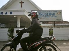 A motorcyclist rides past Gereja Sidang Jemaat Allah (Grace Assembly of God) Church in Medan, North Sumatra, Indonesia, Monday, June 23, 2014. Malaysia's top court ruled Monday that non-Muslims cannot use the word