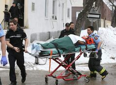 Emergency responders carry a man on a stretcher after there were reports of shots fired on McDermot Avenue this morning.