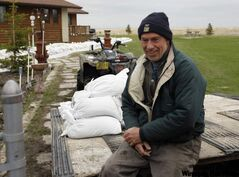 John Caister sits on a trailer waiting to transport sandbags at the home of Foy Dumas, in Twin Lakes Beach.