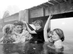 Tammy Holmes and her grandchildren take refuge under a jetty on Friday as a wildfire rages.