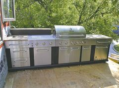 The outdoor kitchen includes a sink, a fridge and a propane barbecue, on a deck nine feet above the yard.
