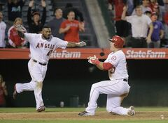 Los Angeles Angels' Mike Trout, right, and Howie Kendrick celebrate after Trout scored on a walk-off double hit by Efren Navarro during the 16th inning of a baseball game against the Seattle Mariners on Saturday, July 19, 2014, in Anaheim, Calif. The Angels won 3-2. (AP Photo/Jae C. Hong)