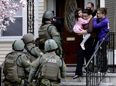 People flee their Watertown home as a SWAT team searches for a suspect in the Boston bombings enters the building Friday.