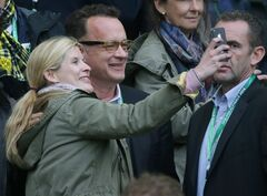 In this picture taken Saturday May 17, 2014, US actor Tom Hanks, second left, and a young woman take a photo during the German soccer cup final between Bayern Munich and Borussia Dortmund at the stadium in Berlin. Actor Tom Hanks has added his voice to those protesting the artificial turf surfaces that Canadian venues will use at the upcoming FIFA 2015 Women's World Cup. THE CANADIAN PRESS/ AP, dpa, Kay Nietfeld