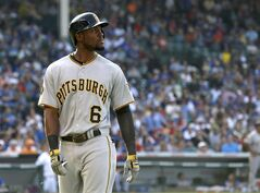 Representing the tying run, Pittsburgh Pirates' Starling Marte looks back out into right field after his long fly ball was caught by Chicago Cubs right fielder Nate Schierholtz, near the warning track during the seventh inning of a baseball game Friday, June 20, 2014, in Chicago. (AP Photo/Charles Rex Arbogast)