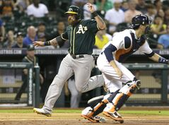Oakland Athletics' Jonny Gomes, left, heads for home to score on a Nate Freiman double as Houston Astros catcher Jason Castro looks for the throw in the fourth inning of a baseball game Tuesday, Aug. 26, 2014, in Houston. (AP Photo/Pat Sullivan)
