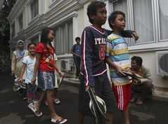 Indonesian children carry pairs of sandals to the office of Indonesian Commission for Child Protection in Jakarta, Indonesia, Tuesday, Jan. 3, 2012, to help protest for a 15-year-old boy who is being prosecuted for lifting an old pair of sandals in Central Sulawesi province. Thousands of Indonesians have dumped flip-flops and other old sandals at police stations and prosecutor offices to show support for the boy who could face up to five years in prison if found guilty, the same sentence given to many terrorists, drug pushers and rapists. (AP Photo/Achmad Ibrahim)