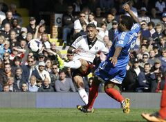 Fulham's Ashkan Dejagah, left, scores a goal past Hull's Tom Huddlestone during the English Premier League soccer match between Fulham and Hull City at Craven Cottage stadium in London, Saturday, April 26, 2014. (AP Photo/Kirsty Wigglesworth)