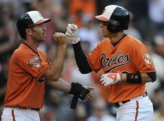 Baltimore Orioles' Manny Machado, right, is congratulated by J.J. Hardy after hitting a two-run home run against the Tampa Bay Rays in the eighth inning of a baseball game, Saturday, June 28, 2014, in Baltimore. The Rays won 5-4. (AP Photo/Gail Burton)